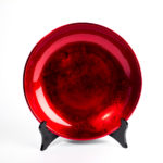Metallic red wooden lacquer serving bowl on black lacquer plate stand.